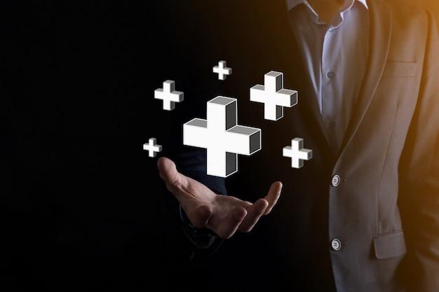 Empresário segurar 3d ícone de adição, homem segurar na mão oferece coisas positivas, como lucro, benefícios, desenvolvimento, rse representado pelo sinal de adição. a mão mostra o sinal de adição.