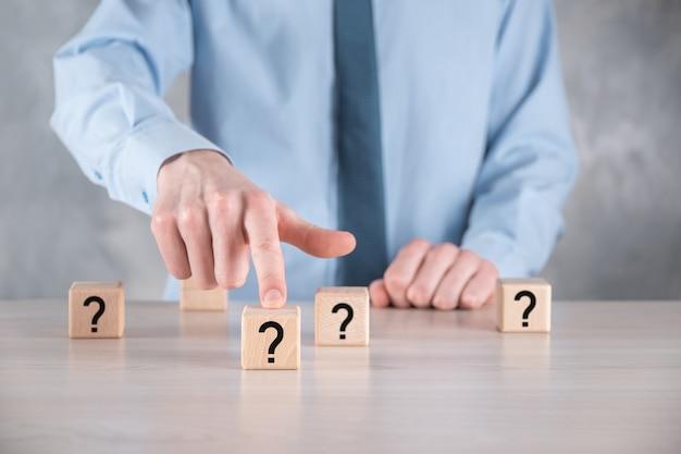 Empresário segurar e colocar a forma de bloco de cubo de madeira com pontos de interrogação na mesa cinza. espaço para text.concept para confusão, dúvida ou solução.