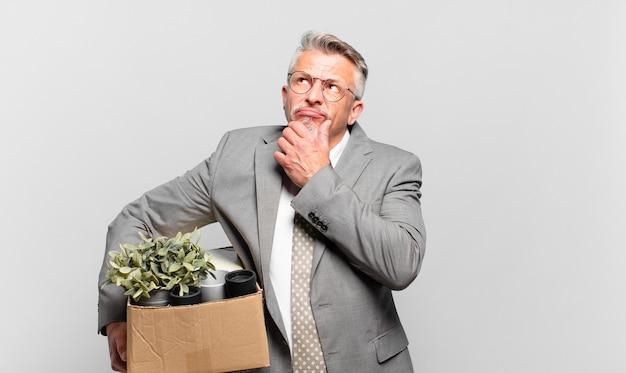 Empresário sênior aposentado pensando, sentindo-se duvidoso e confuso, com diferentes opções, imaginando qual decisão tomar