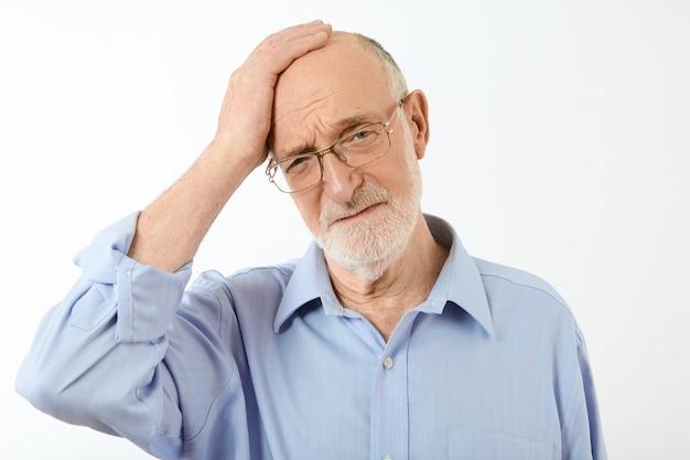Empresário sênior com barba por fazer, óculos retangulares e camisa formal, tendo uma terrível dor de cabeça ou enxaqueca, estressado por causa de problemas de trabalho, com expressão dolorida