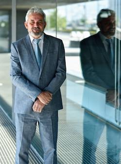 Empresário sênior com os braços cruzados para fora do prédio de escritórios moderno.