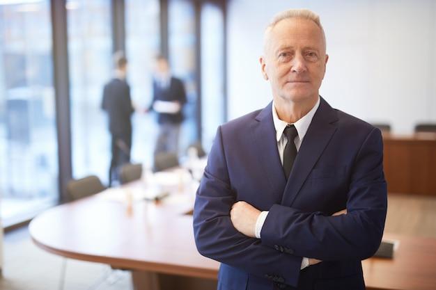 Empresário sênior confiante posando na sala de conferências