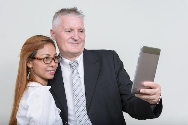 Empresário sênior e mulher de negócios asiática madura juntos contra o branco