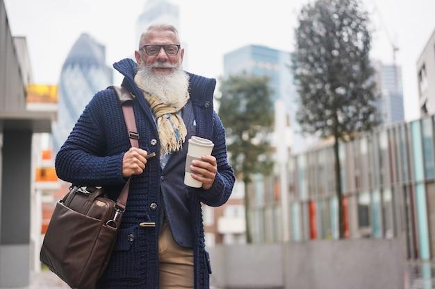 Empresário sênior hippie tomando café na cidade no dia de inverno