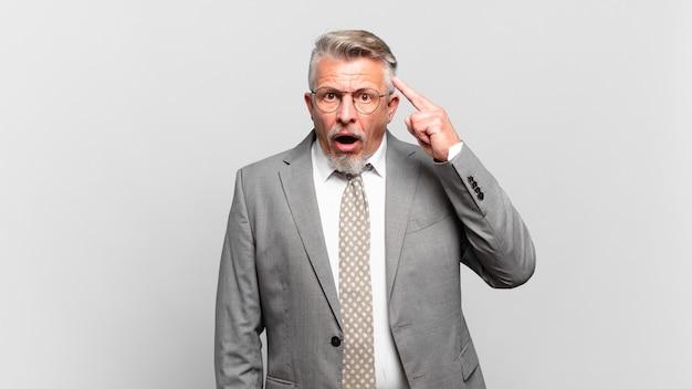 Empresário sênior parecendo surpreso, boquiaberto, chocado, percebendo um novo pensamento, ideia ou conceito