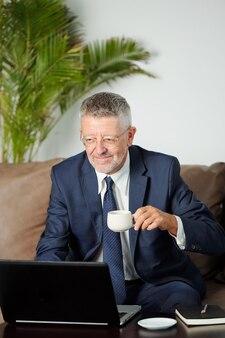Empresário sênior sorridente bebendo café expresso e respondendo a e-mails de clientes ou parceiros de negócios