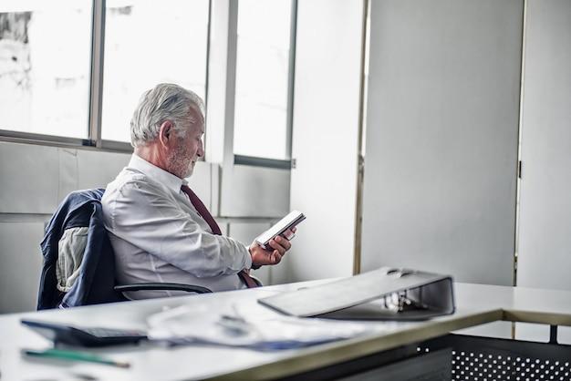 Empresário sênior trabalhando no escritório. usando a internet no telefone inteligente.