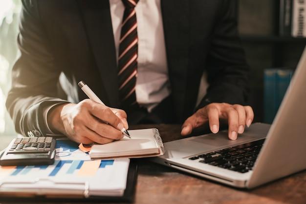 Empresário, sentado à mesa em casa, trabalhando em um laptop e escrevendo ideias em um caderno.