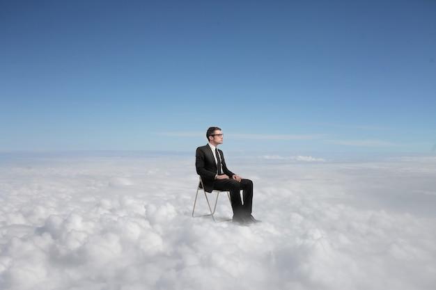 Empresário sentado acima das nuvens