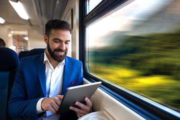 Empresário sentado ao lado da janela, lendo notícias e navegando na internet em seu tablet enquanto viaja no confortável trem de alta velocidade.