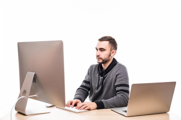 Empresário sentado atrás de uma mesa no trabalho, olhando para o monitor e o laptop sobre o branco