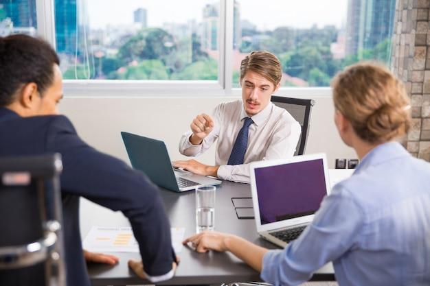 Empresário sentado com um laptop falando com outros colegas