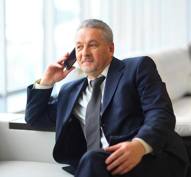 Empresário sentado e falando ao telefone