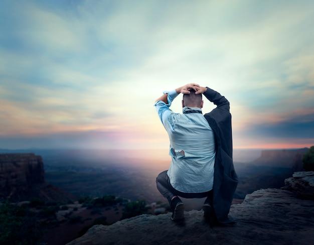 Empresário sentado em desespero na beira da montanha