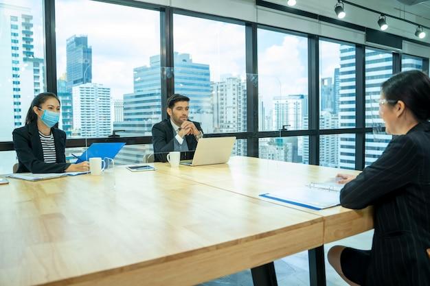 Empresário sentado em entrevista de emprego, retrato de uma jovem mulher tendo uma entrevista de emprego com o gerente e a secretária na empresa financeira.
