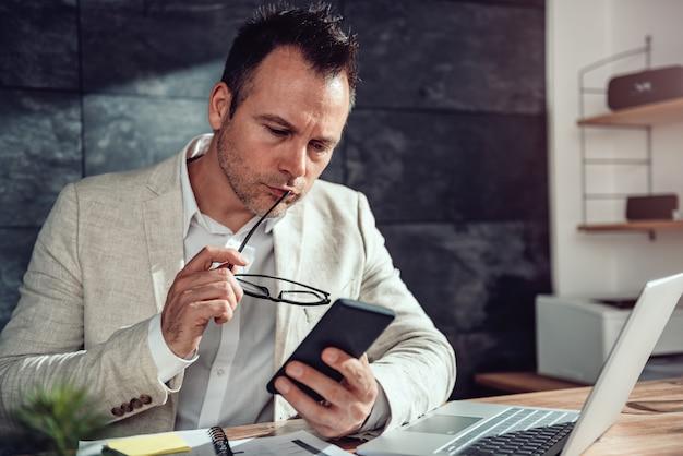 Empresário sentado em sua mesa e lendo mensagens de texto no telefone inteligente