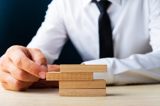 Empresário sentado em sua mesa empurrando um pino em uma pilha deles em uma imagem conceitual de estabilidade de negócios.
