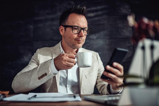 Empresário sentado em sua mesa, tomando café e usando telefone inteligente