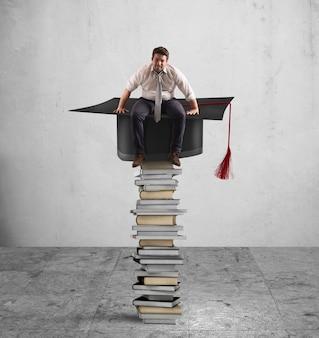 Empresário sentado em uma pilha de livros com chapéu de formatura