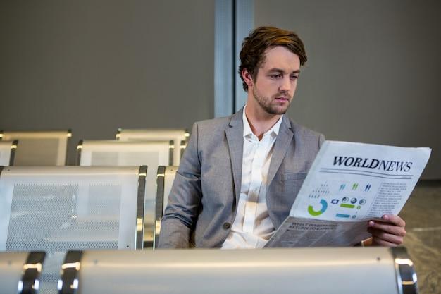 Empresário sentado na área de espera e lendo jornal