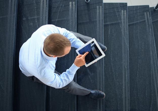 Empresário sentado na escada com tablet eletrônico