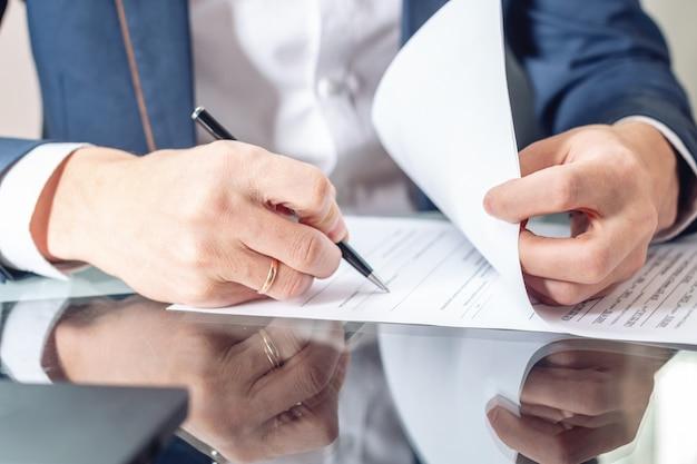 Empresário sentado na mesa assinando documentos no escritório de perto