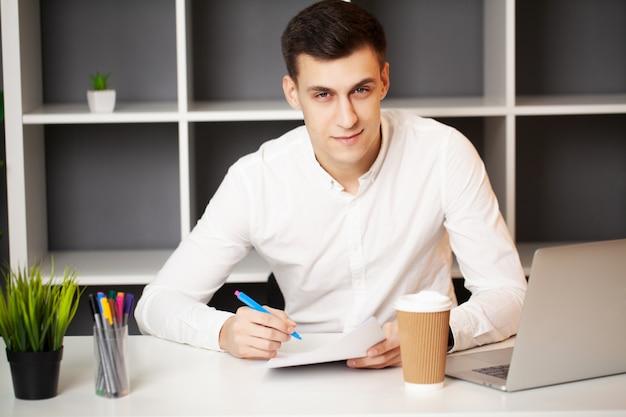 Empresário sentado na mesa de escritório, trabalhando no computador portátil