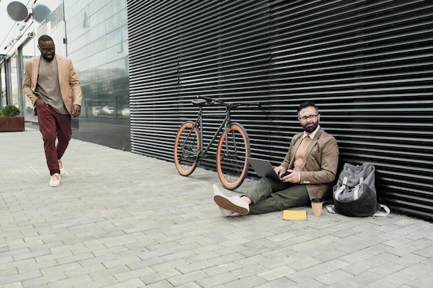 Empresário sentado no chão trabalhando em um laptop com outro homem andando na rua