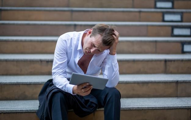 Empresário sentado no degrau mão na cabeça com emoção estressante