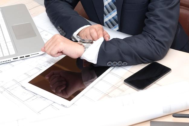 Empresário sentado no escritório e olhando no relógio