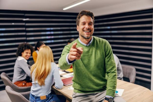 Empresário sentado sobre a mesa na sala de reuniões durante a reunião e apontando para a frente.