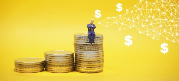 Empresário sentado sobre uma pilha de moedas