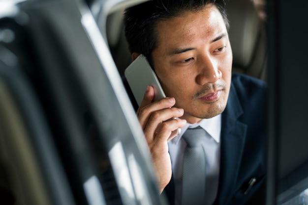 Empresário sente-se dentro do carro use o celular
