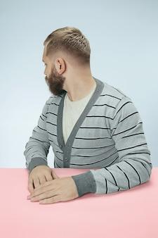 Empresário sério sentado virou-se na mesa sobre fundo azul do estúdio. o retrato em estilo minimalista de perfil