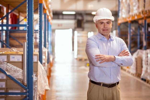 Empresário simpático e confiante olhando para você enquanto está no armazém