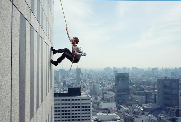 Empresário sobe em um prédio alto com uma corda