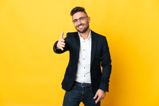 Empresário sobre fundo amarelo isolado apertando as mãos para fechar um bom negócio