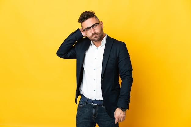 Empresário sobre fundo amarelo isolado com dúvidas