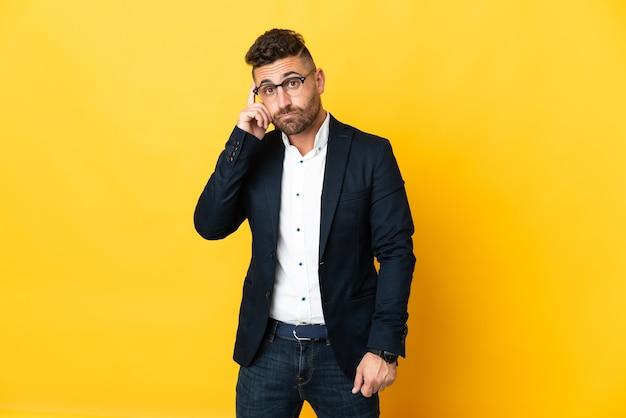Empresário sobre fundo amarelo isolado pensando uma ideia