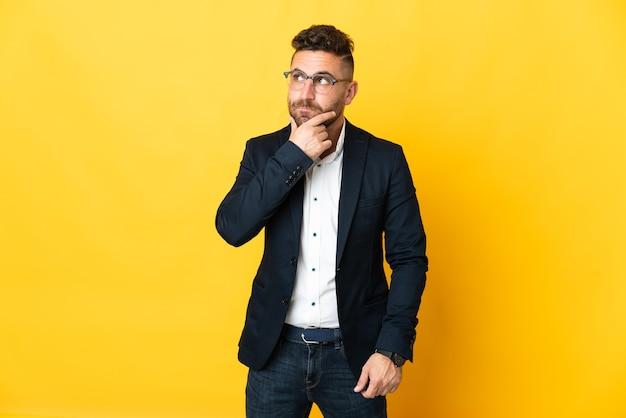Empresário sobre fundo amarelo isolado, tendo dúvidas e pensando