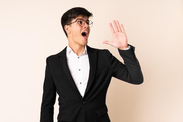 Empresário sobre fundo bege isolado, gritando com a boca aberta