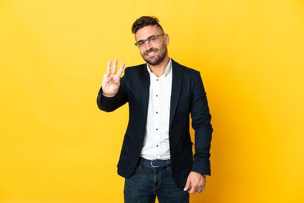 Empresário sobre isolado amarelo feliz e contando três com os dedos