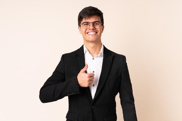 Empresário sobre parede bege, dando um polegar para cima gesto