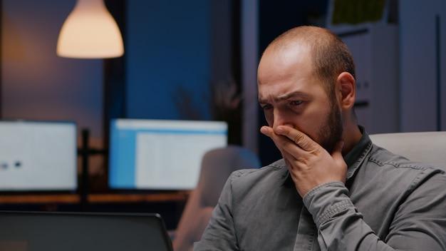 Empresário sonolento trabalhando hora extra em projeto de gerenciamento de prazo corporativo