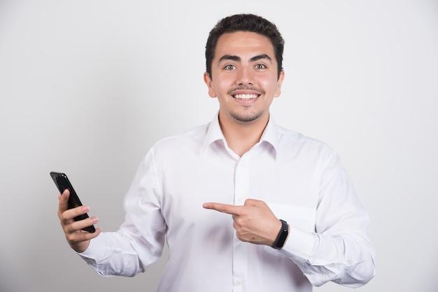 Empresário sorridente, apontando para o telefone em fundo branco.