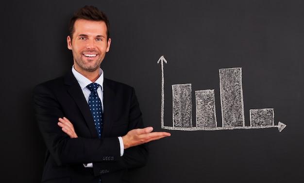 Empresário sorridente apresentando gráfico no quadro-negro