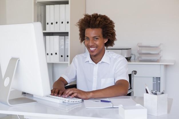 Empresário sorridente casual em cadeira de rodas trabalhando em sua mesa