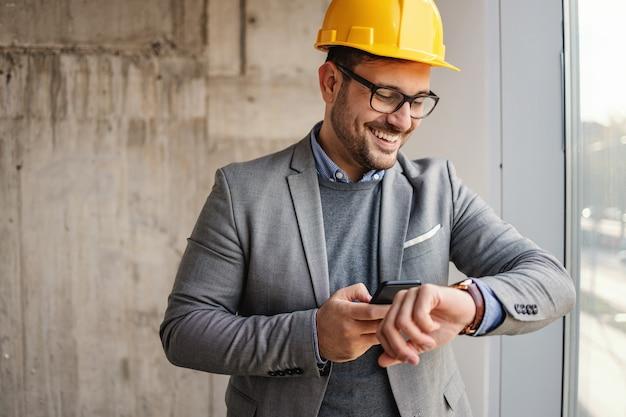 Empresário sorridente com capacete em pé no edifício em processo de construção ao lado de uma janela