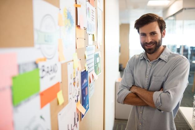 Empresário sorridente com os braços cruzados ao lado de gráficos