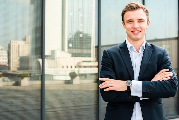 Empresário sorridente com os braços cruzados, olhando para a câmera